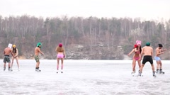 Stock Video Footage of Eight people in underwear skate on natural ice rink at winter