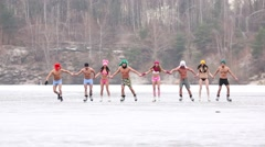 Stock Video Footage of Eight young people skate as chain on natural ice rink at winter