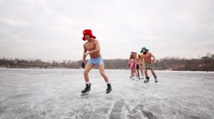Seven young people in underwear skate on natural ice rink as train Stock Footage