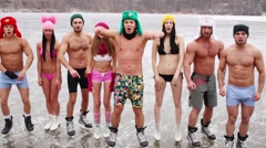Eight people in underwear shout and gesture on ice rink Stock Footage