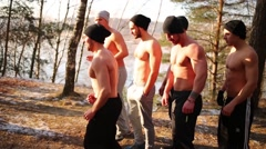 Six half-naked men run in forest near lake at autumn Stock Footage