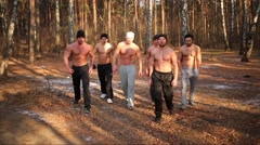 Six half-naked men go in sunny forest at autumn day Stock Footage