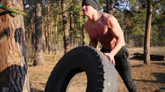 Young half-naked man moves large heavy tire in sunny forest Stock Footage