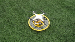 DJI Quadcopter Drone Phantom 3 sits on a mini landing pad on green grass, idle, Stock Footage