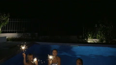 Family or friends with Bengal lights in the pool - stock footage
