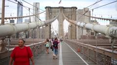 Tourists walk on Brooklyn Bridge - one of oldest suspension bridges in US Stock Footage