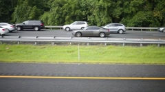 Speedy motion of cars on high way among trees at summer day - stock footage