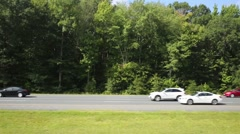 Speedy motion of cars on high way among green trees at summer day - stock footage