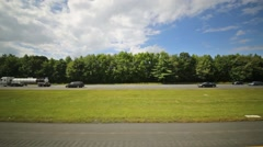 Speedy motion of cars on high way among green trees at sunny day - stock footage