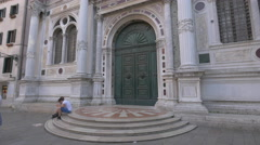 Two people sitting down in front of Scuola Grande di San Rocco, Venice Stock Footage
