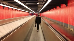 Back of woman going on moving travelator in red hallway Stock Footage