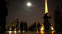 People dancing near Eiffel Tower at moonlit night. Stock Footage