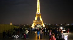 People look at Eiffel Tower at night in Paris, France. Stock Footage
