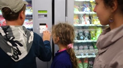 Mother with two children choose snacks from machine Stock Footage