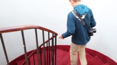 Boy teen goes down stairs on red staircase in building Stock Footage