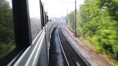 Modern double-decker train travels on rails in summer Stock Footage