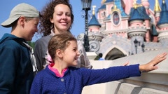 Woman with two children and famous castle in Disneyland Stock Footage