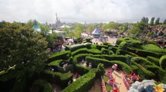 People walk in garden in Fantasyland of Disneyland Stock Footage