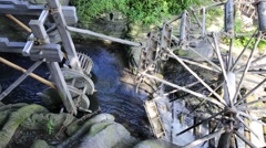 Water mill with wooden wheels on stream at summer day Stock Footage