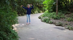 Happy girl dances on path among green trees and bushes in park Stock Footage