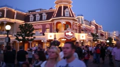 People walk down street at evening in Disneyland in Paris Stock Footage