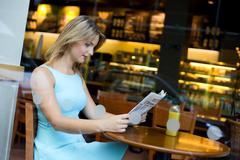 Young woman reading the newspaper in a coffee shop Stock Photos