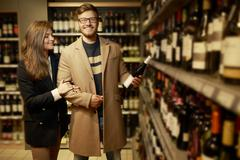 Stock Photo of Couple choosing alcohol in a liquor store