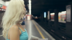 Blonde waiting for train and train arrives millan Stock Footage