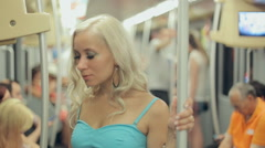 Beautiful blonde standing in a crowded car of the underground in Milan Stock Footage