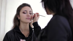 Make-up master brushing eyes with eyeshadow - stock footage