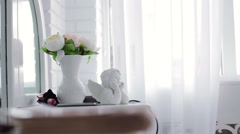 Statuette of Cupid and vase with flowers Stock Footage