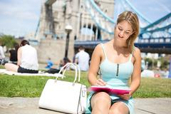 Young woman sitting by tower bridge writing in her agenda. Stock Photos