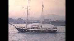 Vintage 16mm film, 1970, Hong Kong, sailboat and kids in skiffs begging - stock footage