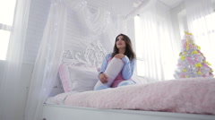 Pretty model in bed with pillows - stock footage