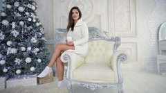 Girl on white armchair near fir-tree - stock footage