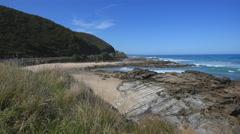 Australia Great Ocean Road rocky outcrop beyond grass Stock Footage