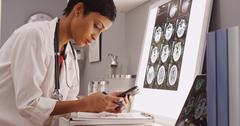 Young attractive doctor texting results of brain scans Stock Photos