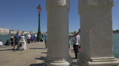 Tourists walking and sitting down on Fondamenta Salute in Venice Stock Footage
