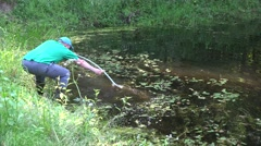 Fish breeding farm worker with scythe tool clean pond from grass. 4K Stock Footage