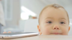 Closeup of baby girl reaching out for smartphone on table Stock Footage