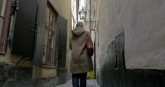 Couple in the narrowest street of Old Town, Stockholm Stock Footage