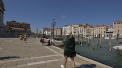 Girl and other tourists sitting down on the shore on Fondamenta Salute, Venice Stock Footage