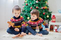 Two adorable children, boy brothers, eating cookies and drinking milk at home - stock photo