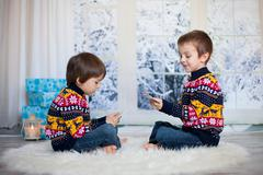 Two adorable children, boy brothers, playing cards at home, wintertime Stock Photos