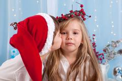 Little brother, giving a kiss to his sister, Christmas concept Stock Photos