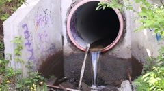 Stock Video Footage of Wastewater pipe with dirty water flowing among debris in city