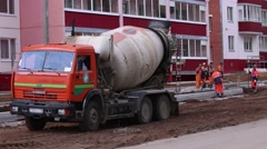 Concrete mixer works on construction and workers stand near it Stock Footage