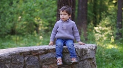 Handsome little boy sits on stone wall in summer park and thinks Stock Footage