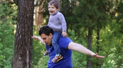 Handsome man plays with his little son in summer park Stock Footage