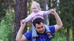 Young handsome man plays with his little cute daughter in summer park Stock Footage